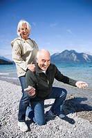 Germany, Bavaria, Walchenseel ,Senior couple fooling about on lakeshore