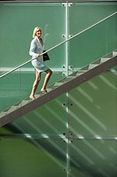 Germany, businesswoman climbing stairs, smiling