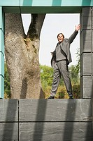 Germany, businessman standing on wall, arms out