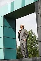 Germany, businessman standing on wall, hand in pocket