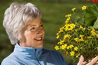 Austria, Senior woman looking at flowers, smiling, portrait