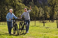 Austria, Karwendel, Senior couple pushing bikes across path