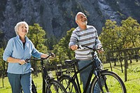 Austria, Karwendel, Ahornboden, Senior couple pushing bikes