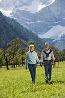Austria, Ahornboden, Senior couple walking across meadow, hand in hand