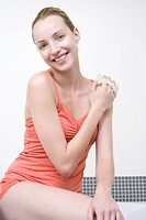 Young woman using massage glove, smiling, portrait