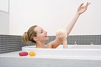 Young woman taking bath, washing arm, side view