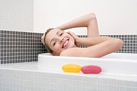 Young woman taking bath, smiling, side view, portrait