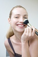 Young woman using make_up brush, smiling, portrait, close_up
