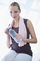 Young woman holding water bottle and towel, portrait