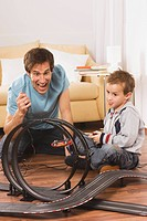 Father and son 4_5 playing with toy racetrack
