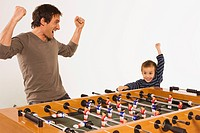 Father and son 4_5 playing tabletop soccer, cheering together