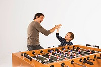 Father and son 4_5 at tabletop soccer, slap hands
