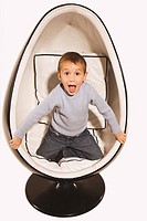 Little boy 4_5 kneeling in design chair, poking his tongue out