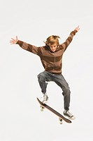 Teenage boy 13_14 performing jump on skateboard, arms out