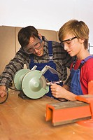 Germany, father and son, Working on grinding machine