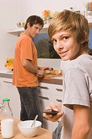 Father and son 13_14, in kitchen, preparing meal
