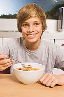 Teenage boy 13_14 having muesli for breakfast, portrait