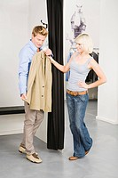 Young couple in changing room, man holding jacket (thumbnail)