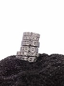 Stacked Diamond rings on black sand