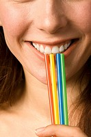 Young woman holding four straws, smiling, close up