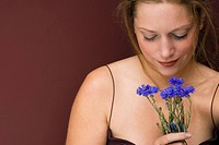 Young woman holding cornflowers, portrait, close up