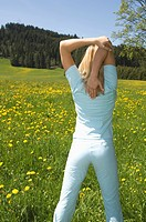 Austria, Salzburger Land, Young woman doing stretching exercise, rear view