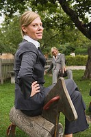 Germany, businesswomen sitting on toy horse in playground