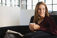 Young woman in office holding cup of coffee, portrait