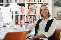 Business woman in office holding cup, smiling, portrait