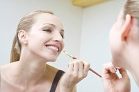 Young woman applying lipstick, smiling, portrait