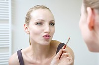 Young woman holding lip brush, puckering lips
