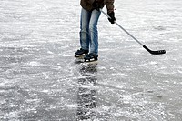 Person playing ice hockey on frozen lake