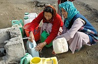 Woman filling jugs of water to transport home Leh, Ladakh, India