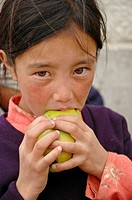 A girl eating a mango Leh, Ladakh, India