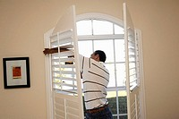 Skilled worker installs white plantation shutter in window