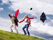 Couple with umbrellas in wind