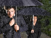 Man and woman with umbrellas, raining