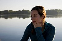 Woman thinking next to lake