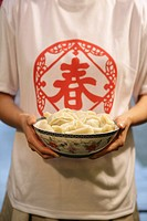 Chinese young woman holding a bowl of Chinese dumpling