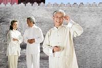 three oriental senior adults doing Taijiquan