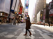 Woman crossing road in Times Square. She is looking towards the sky with a look of amazement.