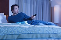 man on hotel bed watching TV