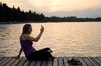 Young woman using cell phone at sunset