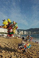 Man selling balloons on beach, Acapulco, Mexico