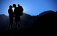 Young couple kissing in setting sun while carrying son on back, Sierra Nevadas, California