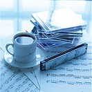 CD cases, cup of coffee and harmonic on sheet music