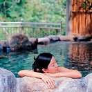 Young woman with eyes closed resting on rim in hot tub