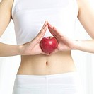 Mid_section of young woman holding apple in front of belly