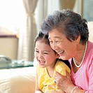 Girl and her grandmother looking at something, smiling