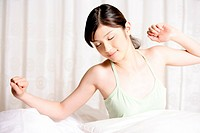 Young woman sitting on bed and stretching